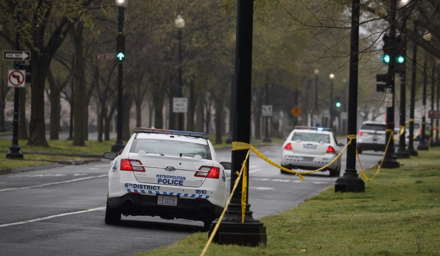 Washington, D.C., Metropolitan Police vehicles park along an empty Independence Avenue and behind yellow police tape near the Tidal Basin and cherry blossoms, in Washington, Monday, March 23, 2020. (AP Photo/Carolyn Kaster) ** FILE **