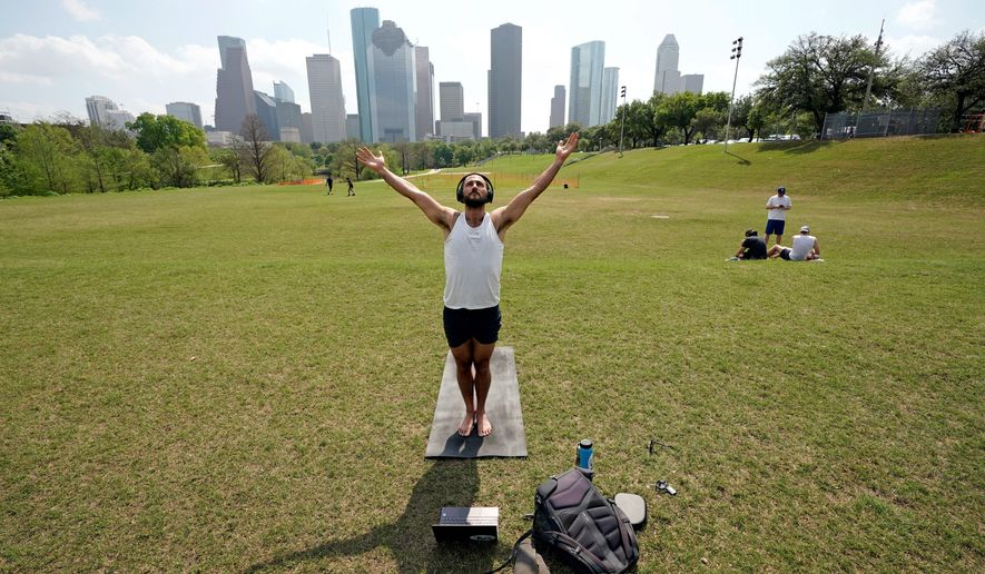 Trey Evans participates in an online yoga class at Eleanor Tinsley Park near downtown Houston, on Tuesday. However, a stay-at-home order was issued for Houston residents, meaning outdoor activities are forbidden in order to stop the spread of the coronavirus. (Associated Press photographs)