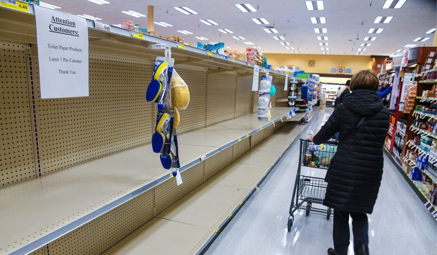 Customers found the shelves empty of toilet paper at a grocery store in Spokane, Washington, last week. More than 6,000 complaints of coronavirus-related price gouging were filed last week with state attorneys-general offices across the country. (The Spokesman-Review via Associated Press)