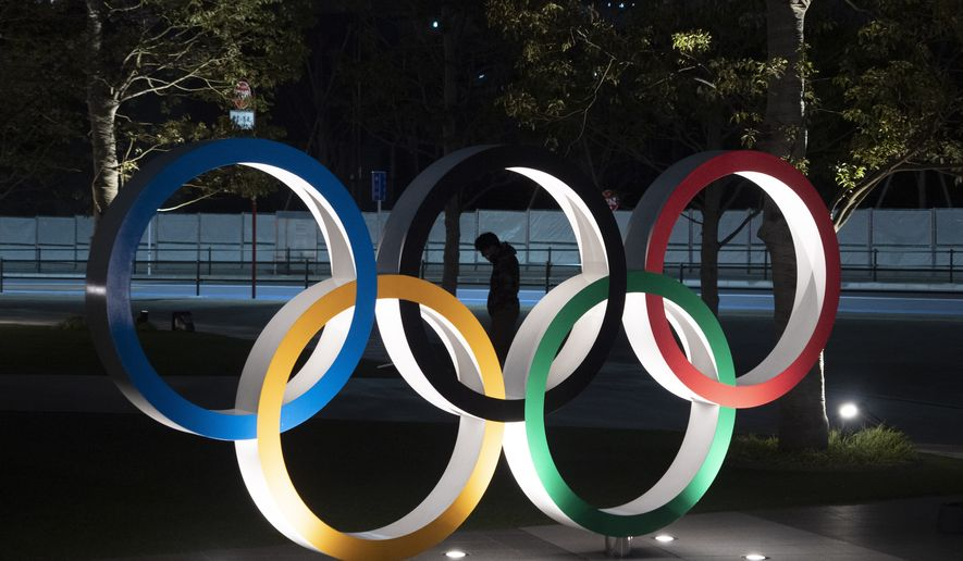 """A man is seen through the Olympic rings in front of the New National Stadium in Tokyo, Tuesday, March 24, 2020. IOC President Thomas Bach has agreed """"100%"""" to a proposal of postponing the Tokyo Olympics for about one year until 2021 because of the coronavirus outbreak, Japanese Prime Minister Shinzo Abe said Tuesday. (AP Photo/Jae C. Hong)"""