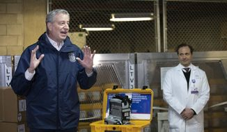 New York City Mayor Bill de Blasio, left, discusses the arrival of a shipment of 400 ventilators with Dr. Steven Pulitzer, the Chief Medical Officer of NYC Health and Hospitals, at the city's Emergency Management Warehouse., Tuesday, March 24, 2020, in New York. (AP Photo/Mark Lennihan)