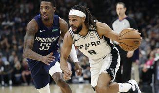 San Antonio Spurs guard Patty Mills (8) drives around Dallas Mavericks guard Delon Wright (55) during the second half of an NBA basketball game in San Antonio, Tuesday, March 10, 2020. (AP Photo/Eric Gay)