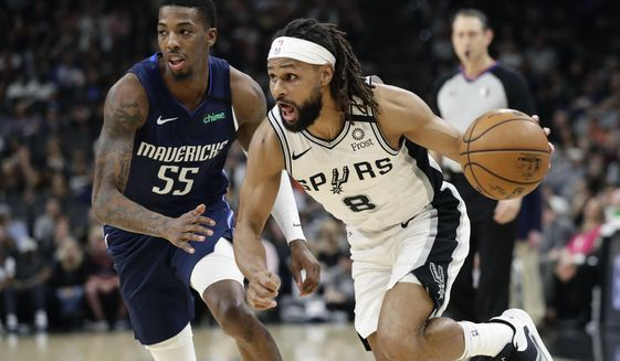 San Antonio Spurs guard Patty Mills (8) drives around Dallas Mavericks guard Delon Wright (55) during the second half of an NBA basketball game in San Antonio, Tuesday, March 10, 2020. (AP Photo/Eric Gay)