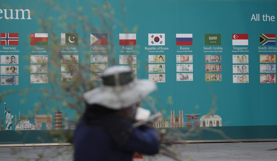 A worker walks near a bank's currency advertisement board in Seoul, South Korea, Tuesday, March 24, 2020. Asian stock markets gained Tuesday after the U.S. Federal Reserve promised support to the struggling economy as Congress delayed action on a $2 trillion coronavirus aid package. (AP Photo/Lee Jin-man)