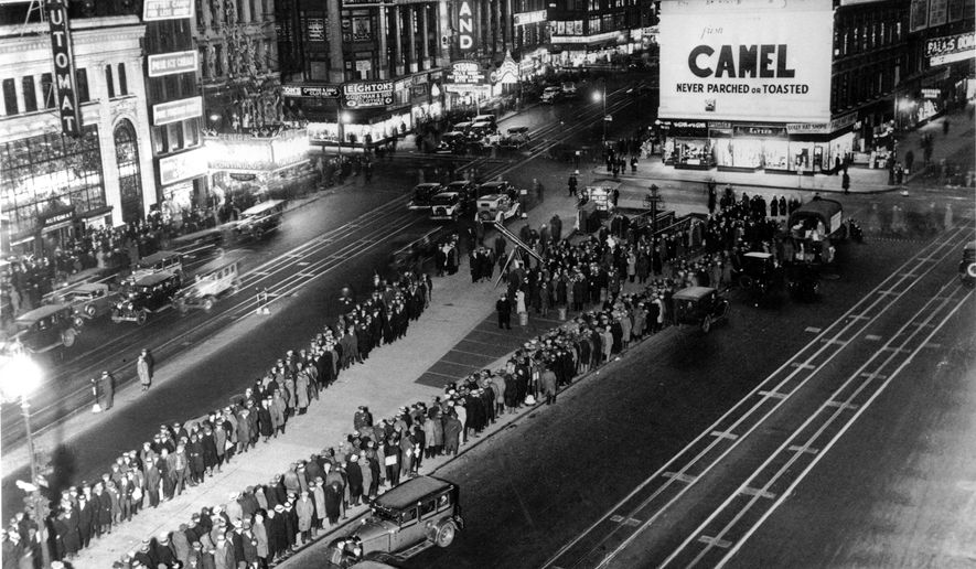 FILE - In this Feb. 13, 1932, file photo, a long line of men wait along Broadway for their ration of a sandwich and a cup of coffee in Times Square in New York City during the Great Depression. Nearly a century later, the U.S. economy is all but shut down, and layoffs are soaring at small businesses and major industries. A devastating global recession looks inevitable. Deepening the threat, a global oil price war has erupted. Some economists foresee an economic downturn to rival the Depression. (AP Photo)