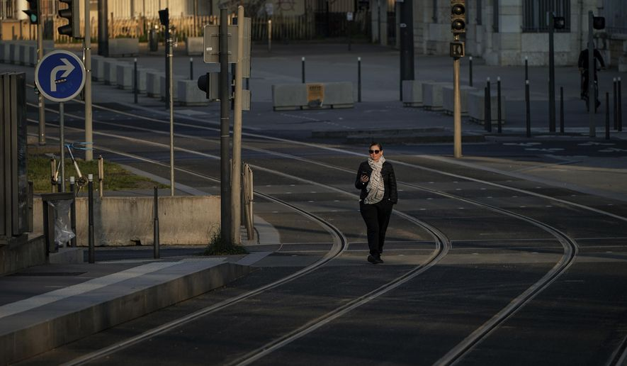 A woman walks on empty tram rails in Lyon, central France, Monday, March 23, 2020. French citizens are only allowed to leave their homes for necessary activities such as shopping for food, going to work or taking a quick walk due to the rapid spreading of the new coronavirus in the country. For most people, the new coronavirus causes only mild or moderate symptoms. For some it can cause more severe illness, especially in older adults and people with existing health problems. (AP Photo/Laurent Cipriani)