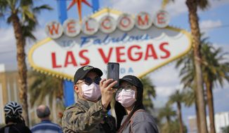 "FILE - In this March 21, 2020 file photo, a couple wearing face masks take a selfie at the ""Welcome to Fabulous Las Vegas Nevada"" sign amid a shutdown of casinos along the Las Vegas Strip due to coronavirus in Las Vegas. The emerging coronavirus pandemic has spurred a lawsuit by a Las Vegas attorney with a background in big cases, who is seeking compensation from the Chinese government for more than 32 million small U.S. businesses that have lost income and profits as a result of the outbreak. Eglet seeks class-action status and said Tuesday, March 24, 2020 he believes damages for Chinese ""reckless"" and ""negligent"" conduct could be in the trillions of dollars. They seek compensation from the government of China. (AP Photo/John Locher, File)"