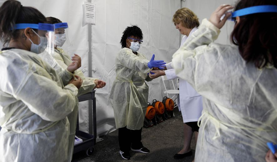 Doctors and healthcare workers with the University of Nevada, Las Vegas School of Medicine suit up in personal protective equipment before taking patients at a drive-through coronavirus testing site Tuesday, March 24, 2020, in Las Vegas. UNLV Medicine, the clinical arm of the UNLV School of Medicine, started conducting COVID-19 testing by appointment for people who meet the Centers for Disease Control and Prevention guidelines. (AP Photo/John Locher)