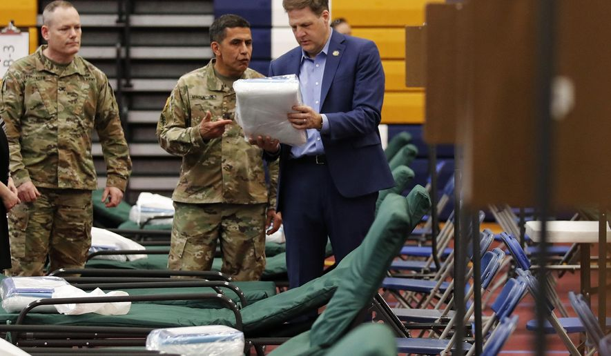 New Hampshire Gov. Chris Sununu, right, examines bedding packets as he tours a makeshift medical facility with N.H. Army National Guard Col. David Mikolaities, center, and N.H.A.N.G. Col. Erik Fessenden, left, at a gymnasium at Southern New Hampshire University in Manchester, N.H., Tuesday, March 24, 2020. The facility, and others across the state, will open when there is demand for patients impacted with COVID-19. For most people, the new coronavirus causes only mild or moderate symptoms. (AP Photo/Charles Krupa)