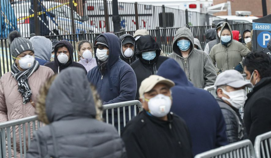 Patients wear personal protective equipment while maintaining social distancing as they wait in line for a COVID-19 test at Elmhurst Hospital Center, Wednesday, March 25, 2020, in New York. (AP Photo/John Minchillo)