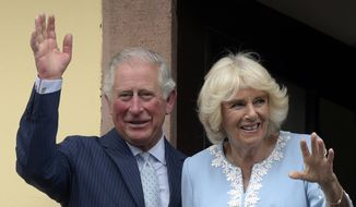 In this Wednesday, May 8, 2019, file photo, Britain's Prince Charles and Camilla, Duchess of Cornwall wave from the town hall balcony in Leipzig, Germany. (AP Photo/Jens Meyer, File)