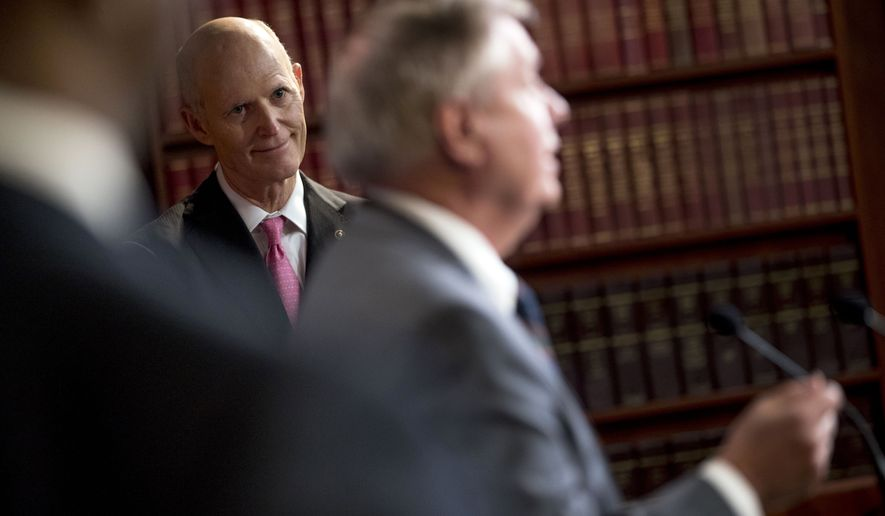 "Sen. Rick Scott, R-Fla., left, listens as Sen. Lindsey Graham, R-S.C., left, speaks at a news conference about the coronavirus relief bill on Capitol Hill in Washington, Wednesday, March 25, 2020. Senators discussed what they are calling a ""drafting error"" in the 2 trillion dollar stimulus bill expected to be voted on today in the Senate. (AP Photo/Andrew Harnik)"
