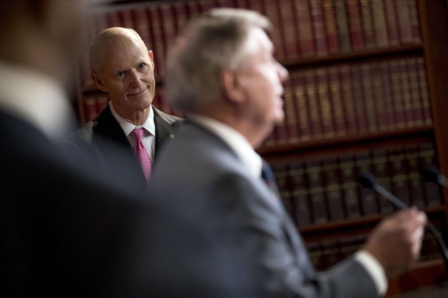 """Sen. Rick Scott, R-Fla., left, listens as Sen. Lindsey Graham, R-S.C., left, speaks at a news conference about the coronavirus relief bill on Capitol Hill in Washington, Wednesday, March 25, 2020. Senators discussed what they are calling a """"drafting error"""" in the 2 trillion dollar stimulus bill expected to be voted on today in the Senate. (AP Photo/Andrew Harnik)"""