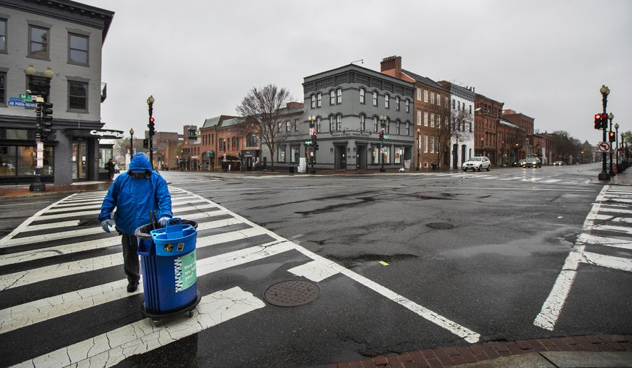 A man crosses the deserted M Street and Wisconsin Avenue NW at the shopping district in Georgetown, Wednesday, March 25, 2020, in Washington. Streets are almost empty in usually crowded and busy shopping areas of capital as Washington residents are urged to stay home to contain the spread of the coronavirus. (AP Photo/Manuel Balce Ceneta)