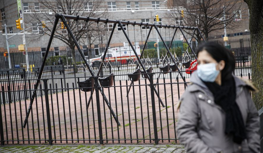 A woman wearing personal protective equipment sits alone alongside empty swings to maintain social distancing at a playground, Wednesday, March 25, 2020, in New York. Gov. Andrew Cuomo sounded his most dire warning yet about the coronavirus pandemic Tuesday, saying the infection rate in New York is accelerating and the state could be as close as two weeks away from a crisis that sees 40,000 people in intensive care. Such a surge would overwhelm hospitals, which now have just 3,000 intensive care unit beds statewide. (AP Photo/John Minchillo)