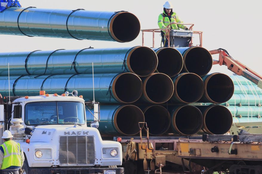 In this May 9, 2015, file photo, workers unload pipes in Worthing, S.D., for the Dakota Access oil pipeline that stretches from the Bakken oil fields in North Dakota to Illinois. A federal judge on Wednesday, March 25, 2020, ordered the U.S. Army Corps of Engineers to conduct a full environmental review of the Dakota Access pipeline, nearly three years after it began carrying oil.  (AP Photo/Nati Harnik, File)