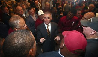 In this Sunday, Dec. 8, 2019, file photo, new Florida State NCAA college football head coach Mike Norvell talks to football staffers after a news conference, in Tallahassee, Fla. Norvell is taking over a Seminoles program that has struggled while he was helping to build Memphis into a Group of Five power. Florida State got in three practices before the new coronavirus outbreak shut down college sports and upended nearly everything else. (AP Photo/Phil Sears, File)  **FILE**