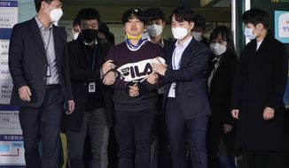 """Cho Ju-bin, center, leader of South Korea's online sexual blackmail ring which is so called """"Nth room,"""" walks out of a police station as he is transferred to prosecutors' office for further investigation in Seoul, South Korea, Wednesday, March 25, 2020. South Korean prosecutors on Wednesday began reviewing whether to formally charge a man arrested last week on allegations he operated secretive chatrooms where he posted sexually abusive videos of blackmailed women in return for cryptocurrency payments. (Kim Hong-Ji/Pool Photo via AP)"""