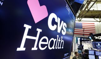 FILE - In this Dec. 4, 2017 file photo, the CVS Health logo appears above a trading post on the floor of the New York Stock Exchange.  CVS Health's Aetna is waiving patient payments for hospital stays tied to the coronavirus. CVS Health's Aetna said Wednesday, March 25, 2020  that many of its customers will not have to make co-payments or other forms of cost sharing if they wind up admitted to a hospital in the insurer's provider network. (AP Photo/Richard Drew, File)