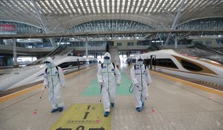 In this photo released by Xinhua News Agency, firefighters conduct disinfection on the platform of Wuhan Railway Station in Wuhan, central China's Hubei Province, March 24, 2020. Chinese authorities said Tuesday they will end a two-month lockdown of most of coronavirus-hit Hubei province at midnight, though the provincial capital will remain closed til April 8, as domestic cases of the virus continue to subside.(Zhao Jun/Xinhua via AP)