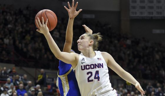 In this Sunday, Jan. 19, 2020, file photo, Connecticut's Anna Makurat (24) shoots during the first half of an NCAA college basketball game against Tulsa, in Storrs, Conn. Makurat, from Poland, is one of more than 20,000 foreign athletes currently competing at NCAA schools, according to the organization. With competition canceled across all NCAA divisions because of the new coronavirus, many of those athletes face a dilemma. Their campuses are shut down, but the coronavirus situation in their homeland may be worse than it is in the United States. (AP Photo/Stephen Dunn, File)  **FILE**