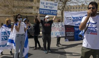 """A man holds a sign, center, that reads, """"Keeping Israel Jewish and democratic,"""" during a protest by supporters of Prime Minister Benjamin Netanyahu, in front of Israel's Supreme Court, in Jerusalem, Tuesday, March 24, 2020. Israel appeared on the verge of a constitutional crisis Tuesday as top members of Benjamin Netanyahu's Likud urged their party colleague and parliament speaker to defy a Supreme Court order to hold an election for the prime minister's successor. (AP Photo/Ariel Schalit)"""