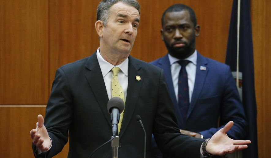 FILE - In this March 11, 2020 file photo, Virginia Gov. Ralph Northam gestures as Richmond Mayor Levar Stoney, back, listens during a news conference at the Capitol in Richmond, Va. In light of the coronavirus pandemic, the governor asked Liberty University President Jerry Falwell Jr. on Wednesday, March 25, 2020, to reconsider his decision to welcome students back to the Lynchburg campus this week after their spring break. (AP Photo/Steve Helber)