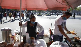 "Lourdes Sanvicente, 45, left, and a coworker wear protective face masks at the direction of the stand's owner, as they sell tamales, sandwiches, and pastries at a street stand in Mexico City, Wednesday, March 25, 2020. Sanvicente, who doubts the existence of the new coronavirus, says both she and her husband work as street food sellers, together earning 320 pesos (around $13.50) per day to support themselves and their five children. ""There is no other option,"" she says, ""I have to provide for my kids."" (AP Photo/Rebecca Blackwell)"