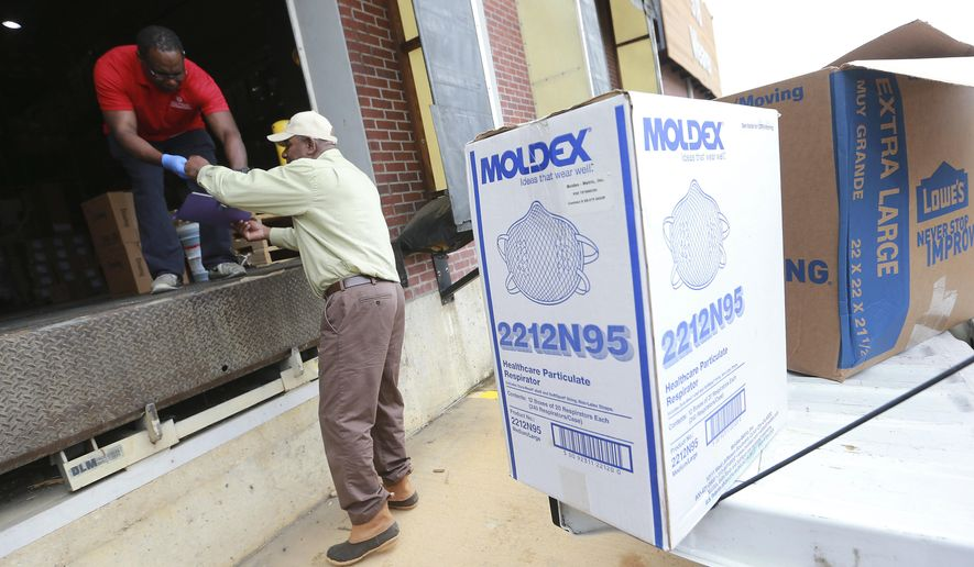 Lee County Emergency Management Coordinator Lee Bowdry, right, drops off boxes full of new N95 face masks to a North Mississippi Medical Center warehouse facility in Tupelo, Miss., Tuesday, March 24, 2020. (Thomas Wells/The Northeast Mississippi Daily Journal via AP)