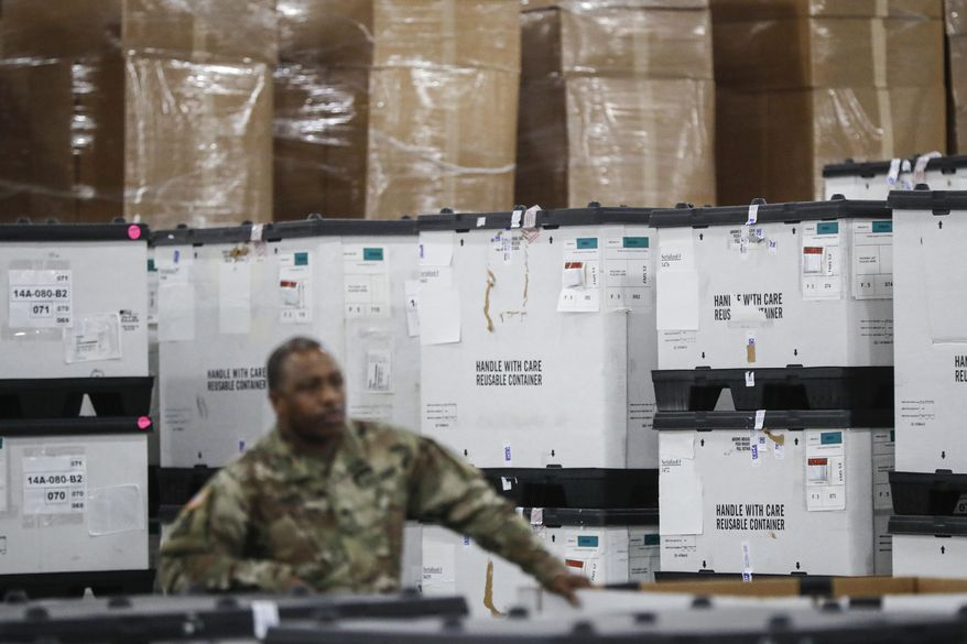 FILE - In this March 23, 2020, file photo, a U.S. National Guard member stands beside crates of medical supplies at the Jacob Javits Center, in New York. The use of National Guard units around the country to help with the response to the coronavirus pandemic is prompting rumors of a national lockdown or even martial law. Guard units are now helping to transport medical supplies, distribute food and even help direct traffic at drive-through testing sites. (AP Photo/John Minchillo, File)