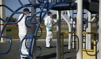 Workers clean and disinfect playground equipment due to the coronavirus outbreak at a park Wednesday, March 25, 2020, in Las Vegas. (AP Photo/John Locher)