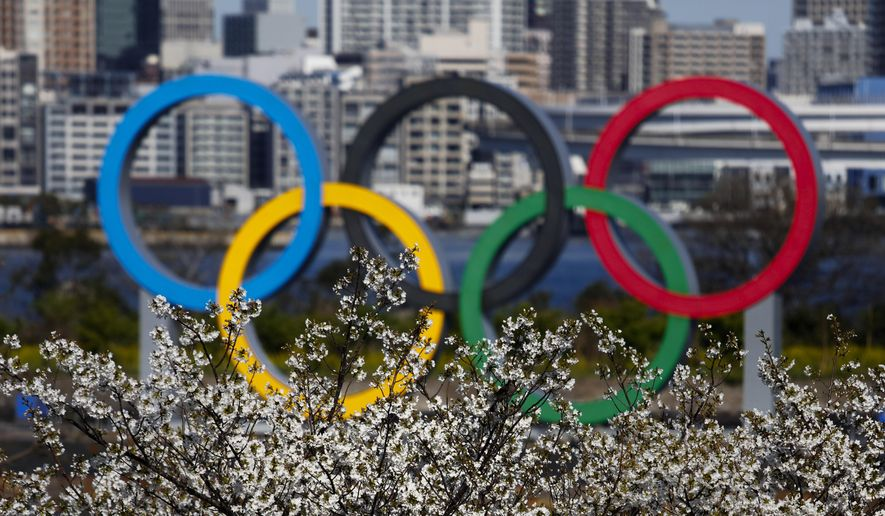 The Olympic rings are seen behind cherry blossoms Wednesday, March 25, 2020, in the Odaiba section of Tokyo. Not even the Summer Olympics could withstand the force of the coronavirus. After weeks of hedging, the IOC took the unprecedented step of postponing the world's biggest sporting event, a global extravaganza that's been cemented into the calendar for more than a century. (AP Photo/Jae C. Hong)