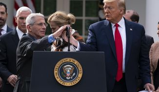 FILE - In this March 13, 2020, file photo Dr. Anthony Fauci, director of the National Institute of Allergy and Infectious Diseases, adjusts the microphone to speak during a news conference on the coronavirus with President Donald Trump in the Rose Garden at the White House in Washington. (AP Photo/Evan Vucci, File)