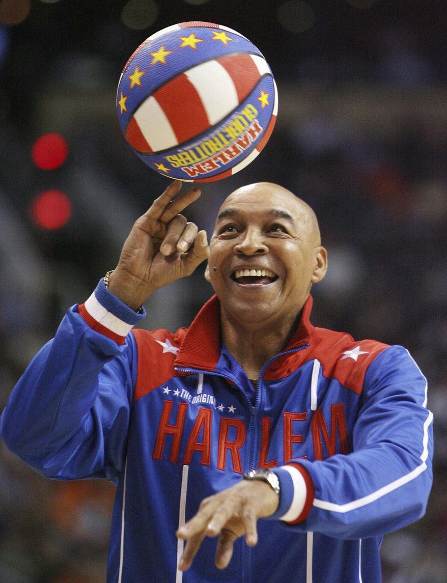 """The Harlem Globetrotters' Fred """"Curly"""" Neal performs during a timeout in the second quarter in an NBA basketball game between the Indiana Pacers and the Phoenix Suns in Phoenix. Neal, the dribbling wizard who entertained millions with the Harlem Globetrotters for parts of three decades, has died the Globetrotters announced Thursday, March 26, 2020. He was 77. Neal played for the Globetrotters from 1963-85, appearing in more than 6,000 games in 97 countries for the exhibition team known for its combination of comedy and athleticism. (AP Photo/Ross D. Franklin, File)  **FILE**"""