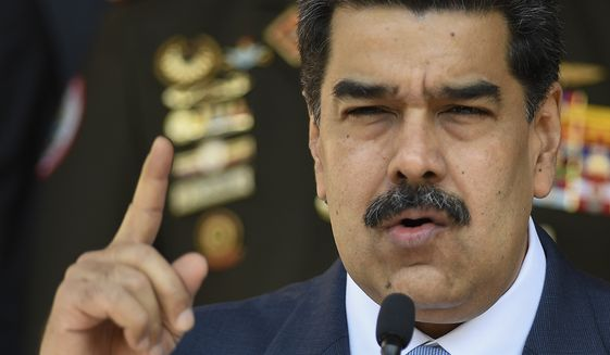In this March 12, 2020, file photo, Venezuelan President Nicolas Maduro speaks at a press conference at the Miraflores Presidential Palace in Caracas, Venezuela. The Trump administration will announce Thursday, March 26, 2020, indictments against Maduro and members of his inner circle for effectively converting Venezuela's state into a criminal enterprise at the service of drug traffickers and terrorist groups, according to multiple people familiar with the situation. (AP Photo/Matias Delacroix, File) **FILE**