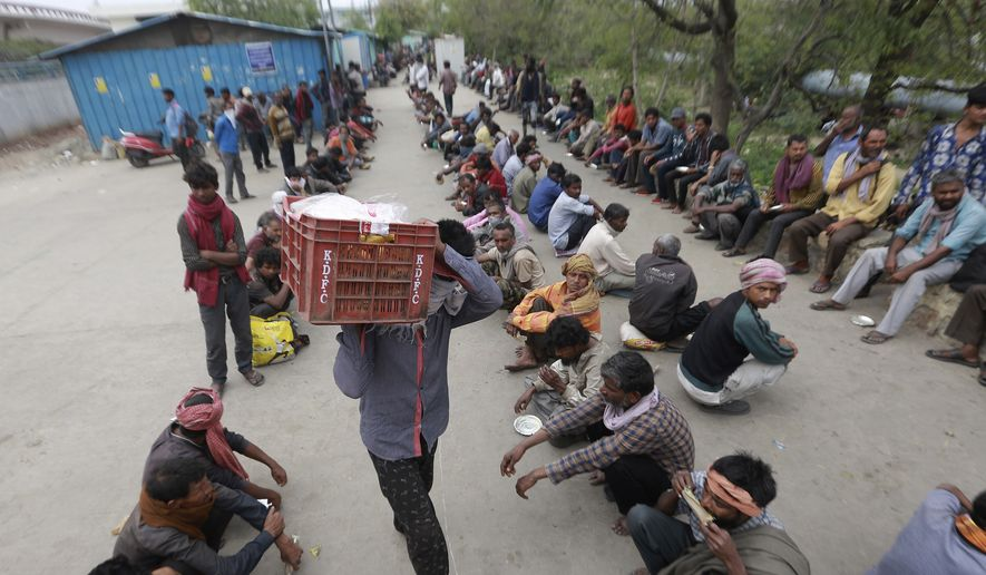 Homeless and impoverished Indians receive food at a government shelter in New Delhi, India, Thursday, March 26, 2020. Some of India's legions of poor and people suddenly thrown out of work by a nationwide stay-at-home order began receiving aid distribution Thursday, as both the public and private sector work to blunt the impact of efforts to curb the coronavirus pandemic. (AP Photo)
