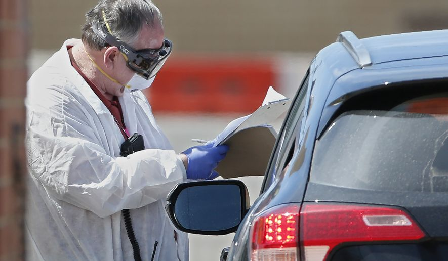 A worker, wearing protective gear, checks in a person at a mobile testing site for COVID-19 in Oklahoma City, Thursday March 26, 2020. The new coronavirus causes mild or moderate symptoms for most people, but for some, especially older adults and people with existing health problems, it can cause more severe illness or death. (AP Photo/Sue Ogrocki)