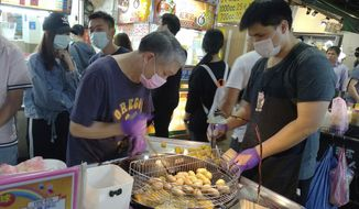 Vendors wear face masks to protect against the spread of the coronavirus and wait for customers at a night market in Taipei, Taiwan, Thursday, March 26, 2020. (AP Photo/Chiang Ying-ying)
