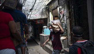 Local volunteers carries packages with soap and detergent to be distributed in an effort to avoid the spread of the new coronavirus in the Rocinha slum of Rio de Janeiro, Brazil, Tuesday, March 24, 2020. (AP Photo/Leo Correa)
