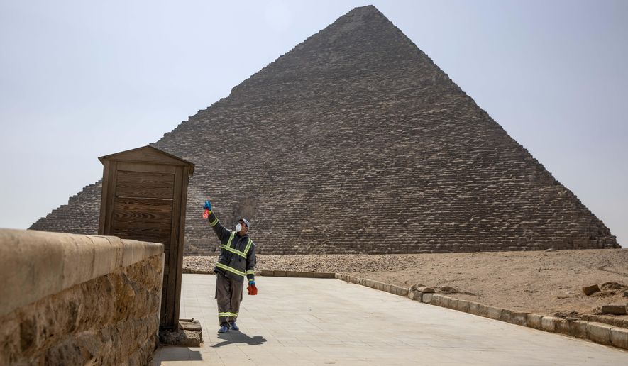 Municipal workers sanitize the areas surrounding the Giza pyramids complex in hopes of curbing the coronavirus outbreak in Egypt, Wednesday, March 25, 2020. The new coronavirus causes mild or moderate symptoms for most people, but for some, especially older adults and people with existing health problems, it can cause more severe illness or death. (AP Photo/Nariman El-Mofty)