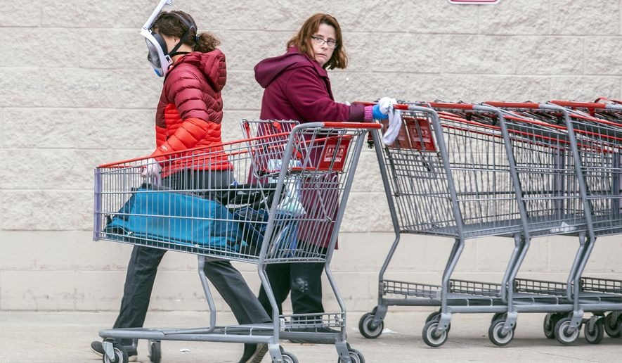 A Costco employee, right, looks towards a shopper wearing a mask and snorkel to go shopping, as she sanitizes carts that are returned from the parking lot to help reduce the spread of coronavirus, in King of Prussia, Pa., Wednesday, March 25, 2020. (Michael Bryant/The Philadelphia Inquirer via AP)