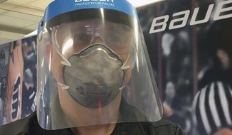 In this March 23, 2020, photo provided by Bauer Hockey Corp., an employee models a medical face shield the hockey equipment manufacturer has begun creating to help those treating the coronavirus pandemic, at Bauer Hockey Corp. in Blainville, Quebec. (Bauer Hockey Corp via AP)