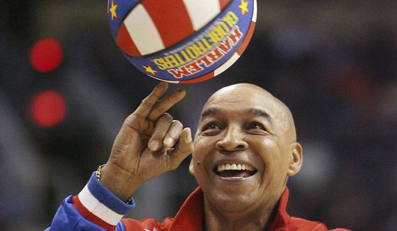 """FILE - In this Jan. 9, 2008, file photo, the Harlem Globetrotters' Fred """"Curly"""" Neal performs during a timeout in the second quarter in an NBA basketball game between the Indiana Pacers and the Phoenix Suns in Phoenix. Neal, the dribbling wizard who entertained millions with the Harlem Globetrotters for parts of three decades, has died the Globetrotters announced Thursday, March 26, 2020. He was 77. Neal played for the Globetrotters from 1963-85, appearing in more than 6,000 games in 97 countries for the exhibition team known for its combination of comedy and athleticism. (AP Photo/Ross D. Franklin, File)"""