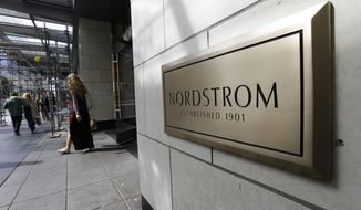 FILE- In this Sept. 13, 2017, file photo, shoppers come and go from Nordstrom Inc.'s flagship store in downtown Seattle.   The outbreak of the coronavirus has dealt a shock to the global economy with unprecedented speed as it continues to spread across the world.   Nordstrom will start to furlough a portion of its corporate employees starting April 5, 2020, for six weeks. It's also extending temporary store closures for at least one week, through April 5. (AP Photo/Ted S. Warren, File)