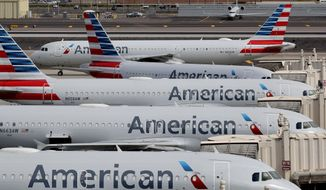 In this Wednesday, March 25, 2020, file photo, American Airlines jets sit idly at their gates as a jet arrives at Sky Harbor International Airport in Phoenix. (AP Photo/Matt York, File)