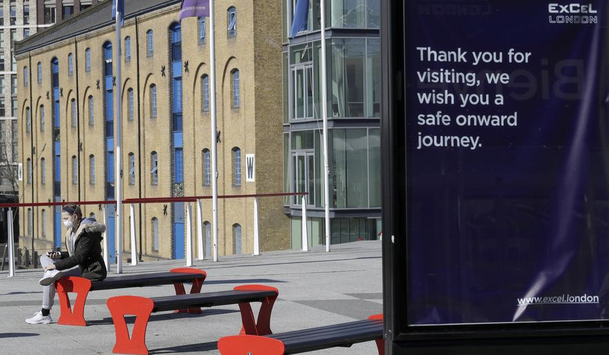 A woman wearing a protective mask sits outside the ExCel centre in London, Wednesday, March 25, 2020. The British Government announced Tuesday, that the ExCel Center in east london will become a 4,000 bed temporary hospital to deal with future coronavirus patients, to be called NHS Nightingale. The new coronavirus causes mild or moderate symptoms for most people, but for some, especially older adults and people with existing health problems, it can cause more severe illness or death.(AP Photo/Kirsty Wigglesworth)