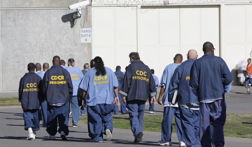 FILE - In this Feb. 26, 2013, file photo, inmates walk through the exercise yard at California State Prison Sacramento, near Folsom, Calif. Public interest attorneys filed an emergency motion, Wednesday, March 25, 2020, asking federal judges to free thousands of infirm and lower-security California prison inmates to prevent a spread of the coronavirus. (AP Photo/Rich Pedroncelli, File)