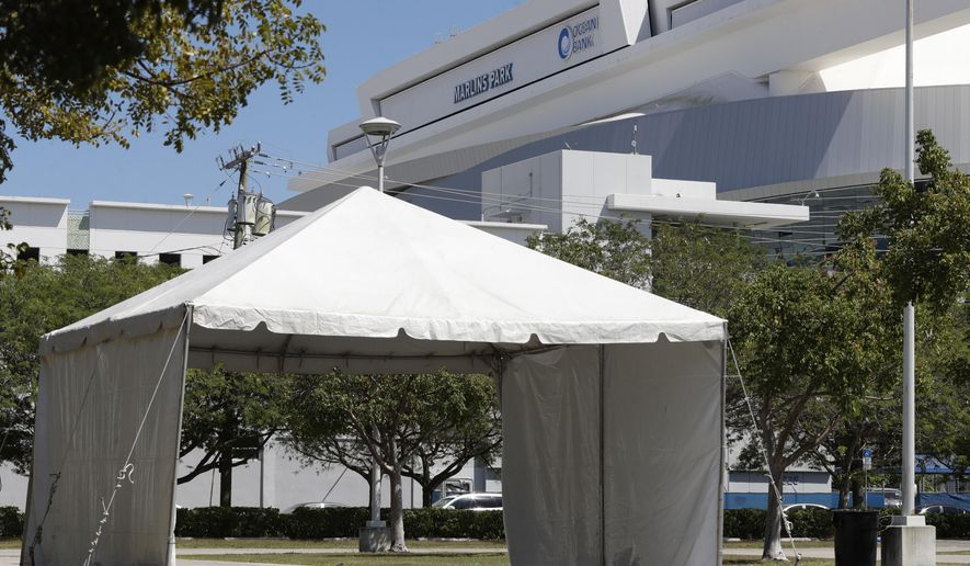 One of several tents set up in a lot in front of the Marlins Park baseball stadium in preparation for a new drive through coronavirus testing site is shown, Monday, March 23, 2020,in Miami. (AP Photo/Wilfredo Lee)