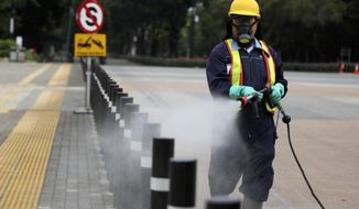 A worker sprays disinfectant at the pedestrian walkway at Senayan Sports Complex amid coronavirus outbreak, in Jakarta, Indonesia, Thursday, March 26, 2020. The new coronavirus causes mild or moderate symptoms for most people, but for some, especially older adults and people with existing health problems, it can cause more severe illness or death. (AP Photo/Dita Alangkara)