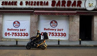 In this Saturday, March 21, 2020 photo, a food delivery scooter passes Barbar Restaurant that now offers food for delivery only, after most of the shops and restaurants closed as part of the preventive measures against the coronavirus, in Beirut, Lebanon. Through 15 years of civil war and various bouts of violence since, Lebanon's Barbar eatery never closed its doors, forging ahead through difficult times while continuously serving up sandwiches to customers -- even if it meant doing so from behind sandbags during the conflict. (AP Photo/Bilal Hussein)